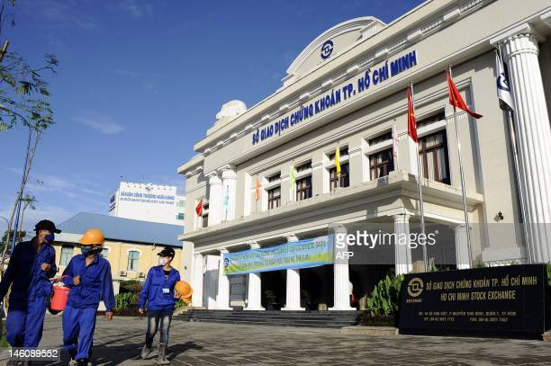 WITH 'VietnambankingeconomyreformFEATURE' by Cat Barton This picture taken on May 28 2012 shows Vietnamese workers walking past the Stock Exchange...