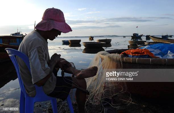 Vietnam-China-Asia-diplomacy-fishing,FEATURE by Cat Barton This picture taken on August 10, 2012 shows a fisherman fixing a net on a fishing beach in...
