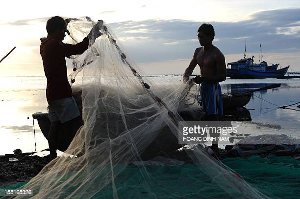 VietnamChinaAsiadiplomacyfishingFEATURE by Cat Barton This picture taken on August 10 2012 shows fishermen preparing nets on a fishing beach in Ly...