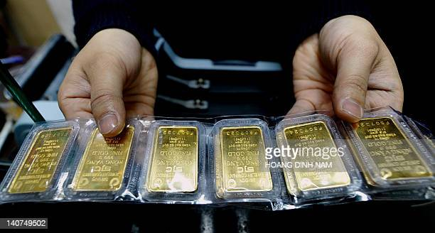 Vietnam-economy-gold,FEATURE by Scott Duke Harris In this file picture taken on February 25 a local gold shop's employee shows off gold bars in...