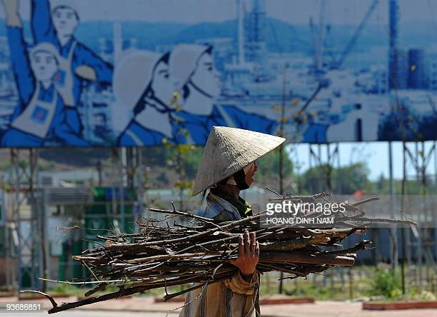 Vietnam-energy-oil-resources-development, by Peter Stebbings A villager collects bushwood for cooking walking past a poster featuring the newly built...