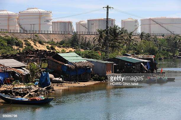 Vietnam-energy-oil-resources-development, by Peter Stebbings Oil tanks of Dung Quat refinery loom over poor families' homes along a river at Dung...