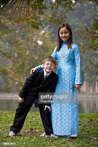 Vietnamese American girl wearing the Vietnamese traditional costume called Ao Dai with her brother at a Christmas party MODEL RELEASED