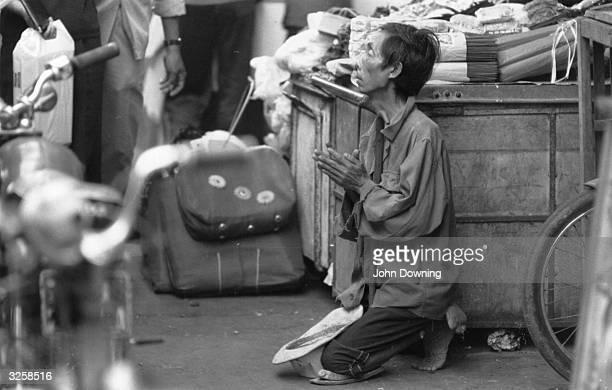 Vietnamese beggar prays for handouts on a South Vietnamese street