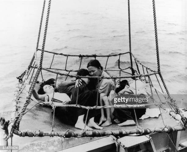 Vietnamese 'boat people' refugees huddle together on a tarp as they are airlifted out of the sea during the Vietnam War 1960s