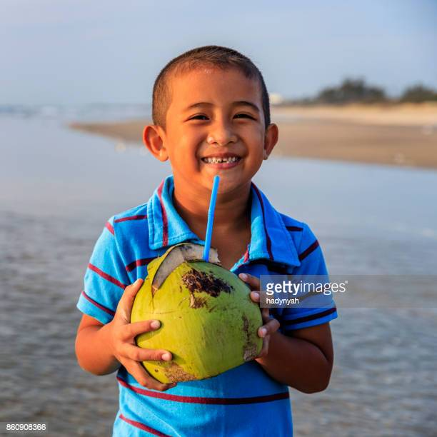 Vietnamese boy holding coconut on the beach, Vietnam