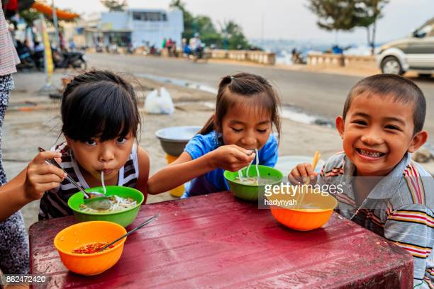 vietnamese children eating a pho bo, south vietnam - traditionally vietnamese stock pictures, royalty-free photos & images