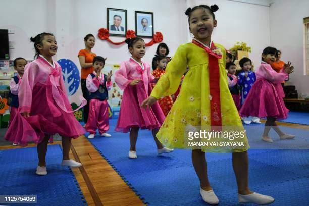 Vietnamese children perform in front of the portraits of the late North Korean leader Kim Il Sung and Vietnam's Ho Chi Minh at the VietnamNorth Korea...