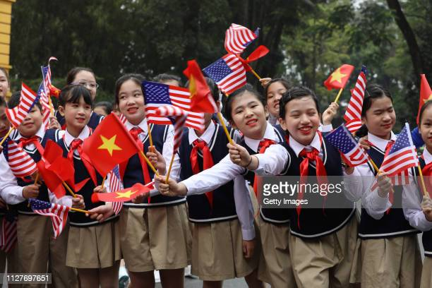 Vietnamese children wave flags before the arrival of US President Donald Trump at the Presidential Palace on February 27 2019 in Hanoi Vietnam US...