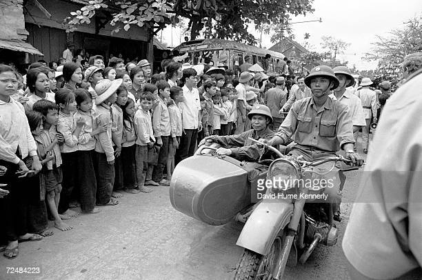 Vietnamese civilians and soldiers wait for the release of American POW's at the Hanoi Hilton March 291973 in Hanoi Vietnam