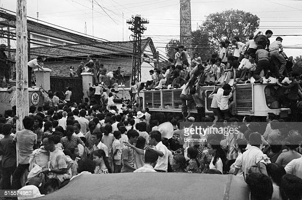 Vietnamese civilians climbing on board a US bus carrying evacuees into the US Embassy while hundreds milled around the gate trying to get in to join...