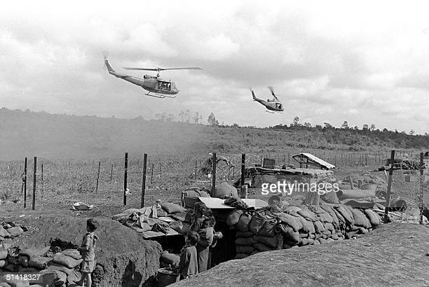 Vietnamese civilians to be evacuated watch helicopters arriving at an American camp in Plei Me south Vietnam 01 November 1965
