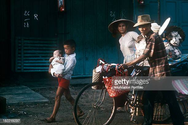 A Vietnamese family fleeing from Saigon after June attack carrying their personal effects on a bicycle Saigon 1968