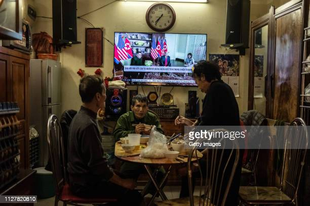 Vietnamese family watches a screen reporting on the US President Trump meeting with North Korean leader Kim Jongun on February 27 2019 in Hanoi...