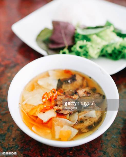 Vietnamese famous noodle soup of grilled pork and rice noodles served with fresh herbs dipping sauce and spring roll