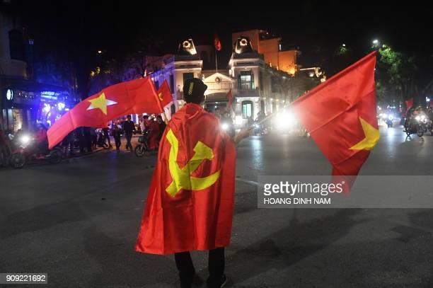 A Vietnamese fan celebrates after the country's U23 team defeated Qatar at the semifinal of the U23 AFC Championship in Hanoi on January 23 2018 /...