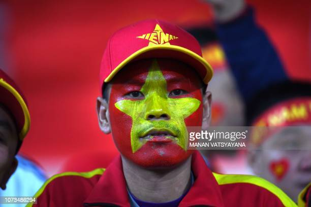 A Vietnamese fan waits for the start of the AFF Suzuki Cup 2018 final football match between Vietnam and Malaysia at the My Dinh Stadium in Hanoi on...