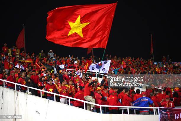 Vietnamese fans cheer before the AFF Suzuki Cup 2018 final football match between Vietnam and Malaysia at the My Dinh Stadium in Hanoi on December 15...