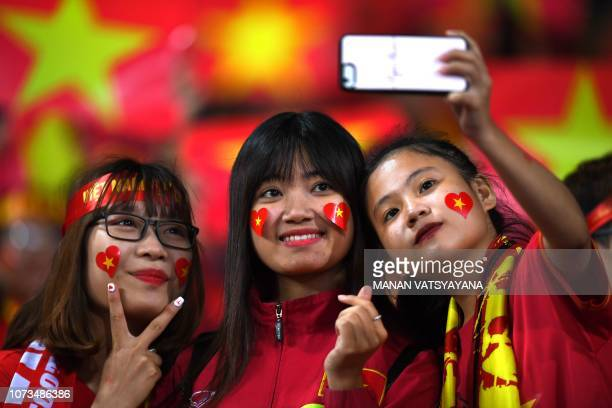 Vietnamese fans pose for a selfie before the start of the AFF Suzuki Cup 2018 final football match between Vietnam and Malaysia at the My Dinh...