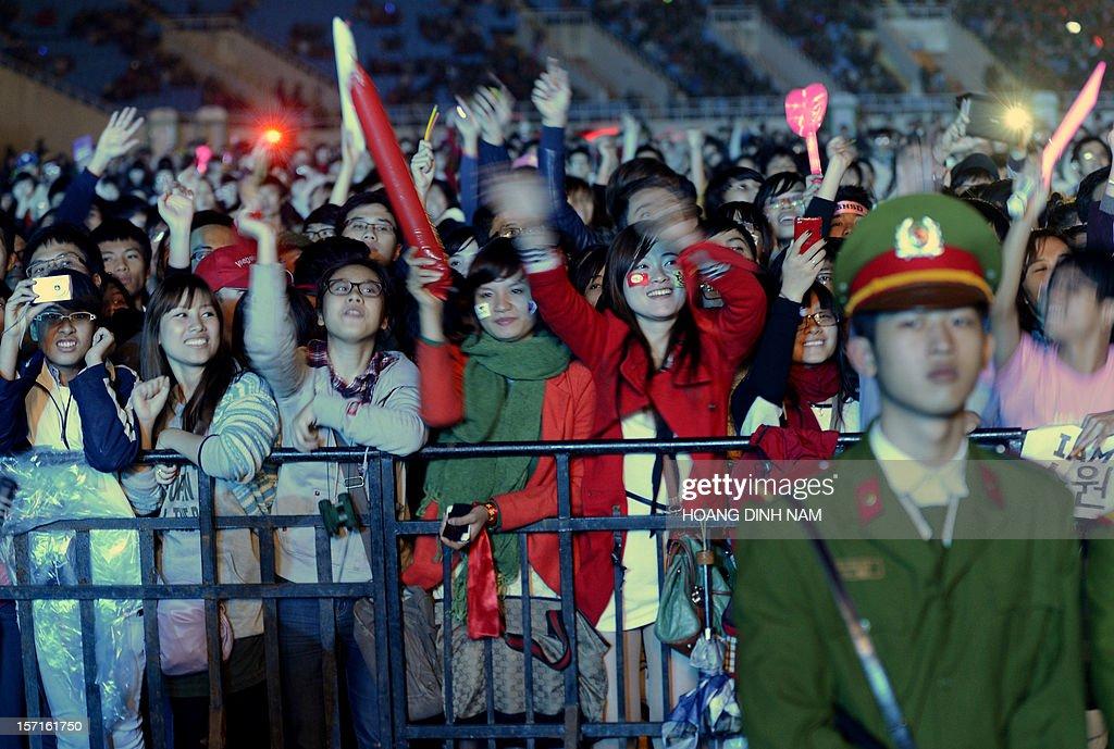 Vietnamese fans watch SKorean K-pop bands performing during a concert held at Hanoi's My Dinh stadium on November 29, 2012. Seventeen SKorean pop bands performed at the concert held to mark the 20th anniversary of the establishment of diplomatic ties between South Korea and Vietnam. AFP PHOTO/HOANG DINH Nam