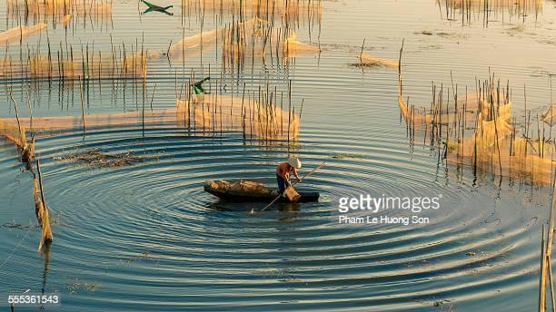 Vietnamese fisher man working on the lake