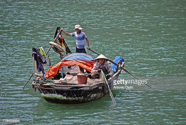 Vietnamese fishermen in Ha Long Bay. They live in floating villages in the bay in the Gulf of Tonkin. It includes about 3000 limestone islands with...