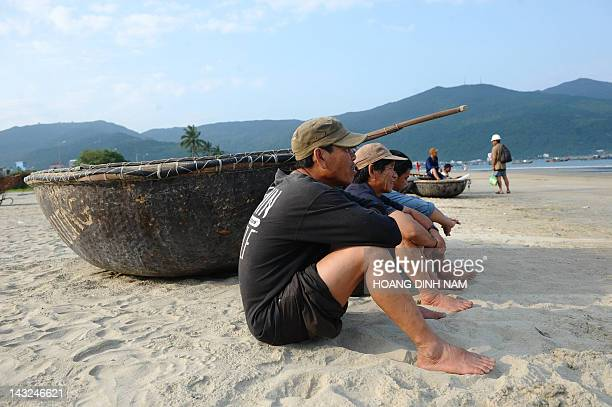 Vietnamese fishermen sit waiting to leave for a night fishing trip from a beach in the central city of Danang on April 22, 2012. Vietnam and the US...