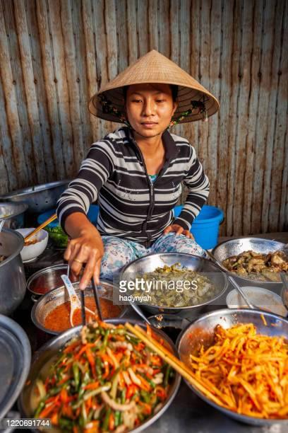 vendeur d'aliments vietnamiens sur le marché local - chapeau chinois photos et images de collection