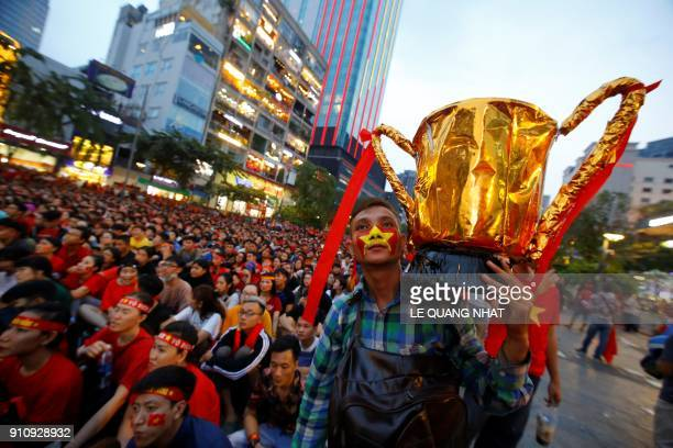 Vietnamese football fan holds a mock cup while watching a television broadcast in Ho Chi Minh city on January 27 2018 showing the 2018 AFC U23...