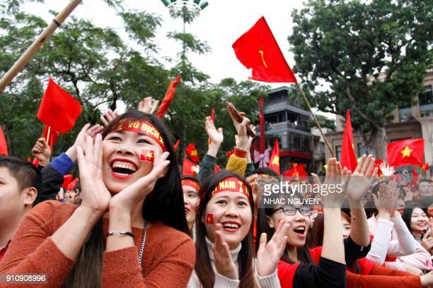 Vietnamese football fans cheer for the Vietnamese team as they watch a television broadcast in Hanoi on January 27 2018 showing the 2018 AFC U23...