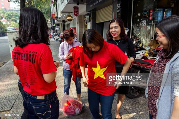 Vietnamese football fans don tshirts emblazoned with the colors of the national flag in a street in Ho Chi Minh city on January 27 2018 prior to...