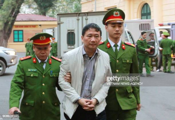 Vietnamese former state oil executive Trinh Xuan Thanh is led toward a courtroom for the verdict in his trial at Hanoi's People's Court on January 22...