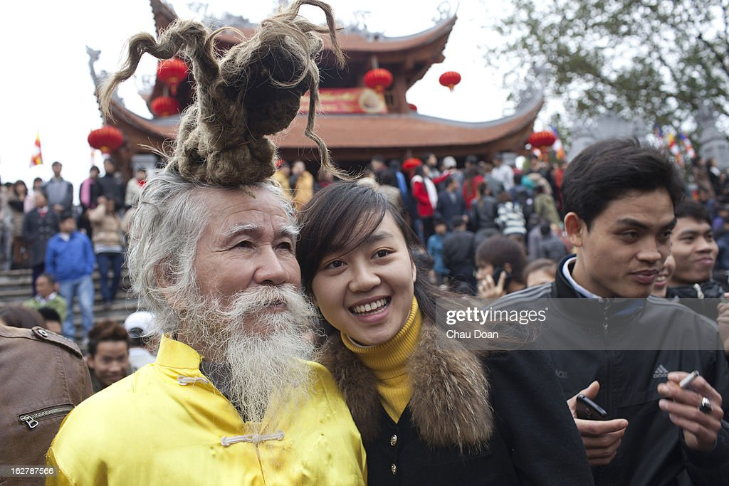 Vietnamese girl poses for photo with an old man who has an unique hairstyle at the Lim festival. The Lim festival takes place at the 13th day of the first lunar month in Lim village, about 18 kilometers from Hanoi. This is one of the most well-known festivals in Vietnam when folk songs called Quan Ho are performed. The legend says that a woman named Ba Mu, who attained enlightenment after becoming a Buddhist monk at the Lim pagoda, had ended a drought in the village on the request of the villagers. Henceforth the people of the village worshipped her as their protector and took the date of her enlightenment as the date of the festival in Vietnam. Quan Ho is the dialog performance between male singers and female singers. The singers have to be quick witted and have strong grasp of traditional tunes, history and meaning of the songs..