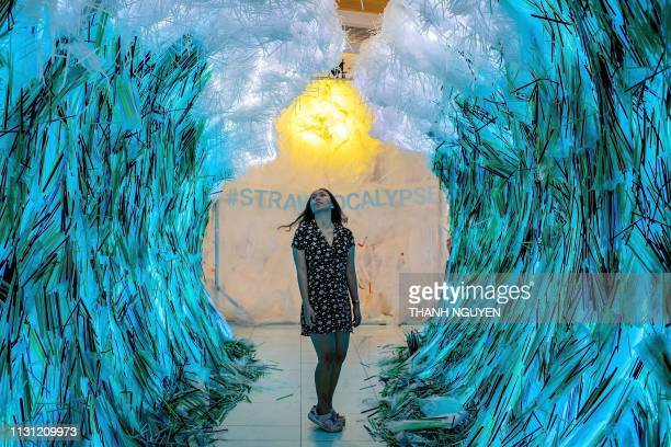 A Vietnamese girl poses for photographs amidst the The Parting of the Plastic Sea art installation made out of plastic straws by Canadian artist...