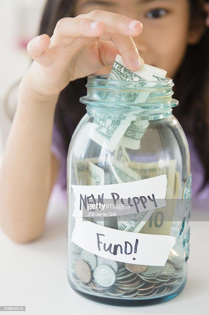 Vietnamese girl saving money in new puppy fund : Stock Photo