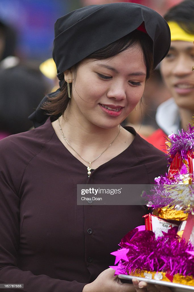 Vietnamese girl wearing a traditional costume at the Lim festival. The Lim festival takes place at the 13th day of the first lunar month in Lim village, about 18 kilometers from Hanoi. This is one of the most well-known festivals in Vietnam when folk songs called Quan Ho are performed. The legend says that a woman named Ba Mu, who attained enlightenment after becoming a Buddhist monk at the Lim pagoda, had ended a drought in the village on the request of the villagers. Henceforth the people of the village worshipped her as their protector and took the date of her enlightenment as the date of the festival in Vietnam. Quan Ho is the dialog performance between male singers and female singers. The singers have to be quick witted and have strong grasp of traditional tunes, history and meaning of the songs..
