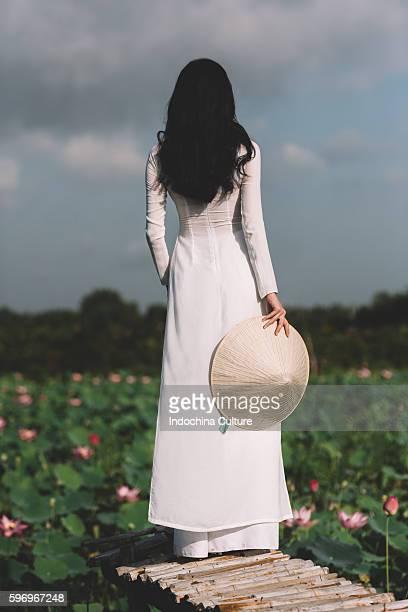 Vietnamese girl wearing Ao Dai (Long Dress) at Lotus pond