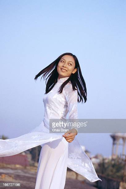 Vietnamese girl wearing the traditional Vietnamese costume called 'Ao Dai' poses for a portraiture shoot