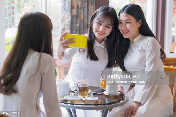 vietnamese girlfriends in traditional dress having coffee together - vietnamese culture stock pictures, royalty-free photos & images