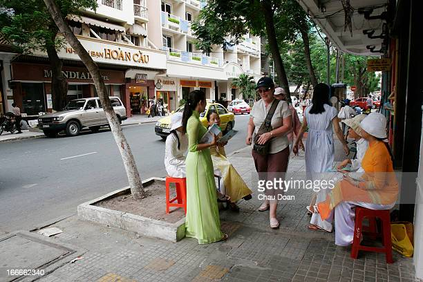 Vietnamese girls give foreign tourists the advertisements of the massage service in Ho Chi Minh City