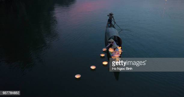 HUE, VIETNAM, APRIL 17, 2016: Vietnamese girls with Ao Dai are lighting candle in lantern to pray in the river. Ao dai is famous traditional custume for woman in VIetnam.