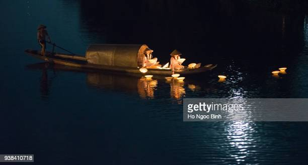 HUE, VIETNAM, APRIL 17, 2017: Vietnamese girls with Ao Dai are lighting candle in lantern to pray in the river. Ao dai is famous traditional custume for woman in VIetnam.