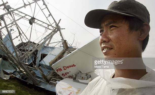 Vietnamese immigrant Loc Nguyen stands by a brother's shrimp boat which was damaged by Hurricane Katrina February 23 2006 in Empire Louisiana Katrina...