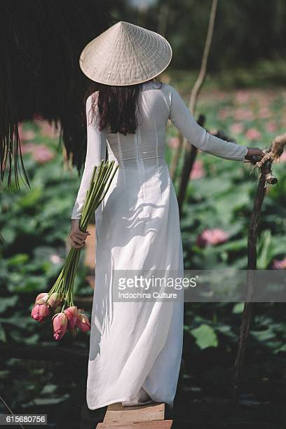 vietnamese lady wearing ao dai (long dress) at lotus pond - long dress stock pictures, royalty-free photos & images