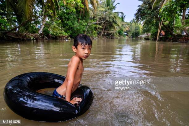 Vietnamese little boy bathing in Mekong River Delta, Vietnam