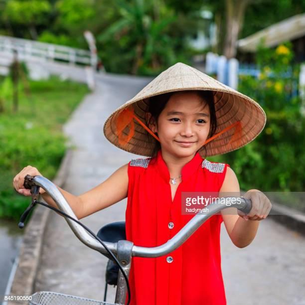 Fillette vietnamienne tenant un bicyclette, Delta du Mekong, Vietnam