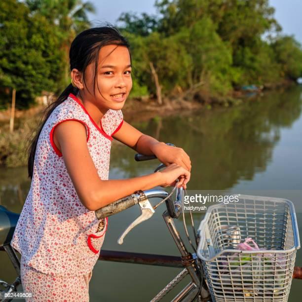 Vietnamese little girl riding a bicycle, Mekong River Delta, Vietnam