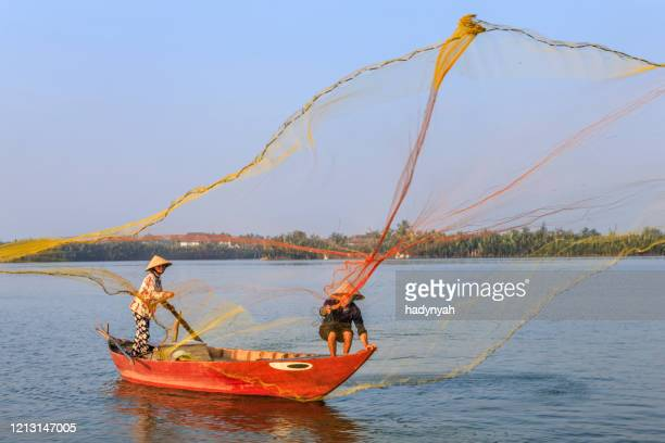vietnamese man catching fishes in thu bon river near hoi an, central vietnam - south vietnam stock pictures, royalty-free photos & images