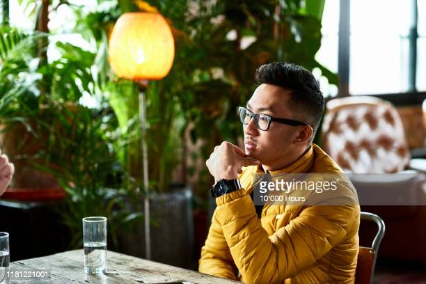 vietnamese man listening to friend in cafe - asian stock pictures, royalty-free photos & images