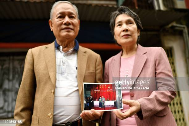 Vietnamese man Pham Ngoc Canh and his North Korean wife Ri Yong Hui pose together holding their wedding photograph outside their house in Hanoi on...